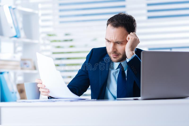 Trött erfaren borrad chefkänsla, medan läsa dokumenten royaltyfri foto