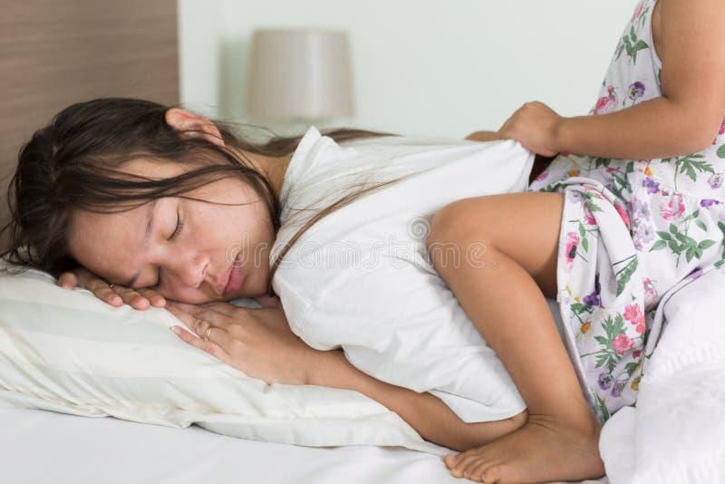 Trött förälder som försöker att ta för att sova med hennes barn som besvärar henne arkivbilder