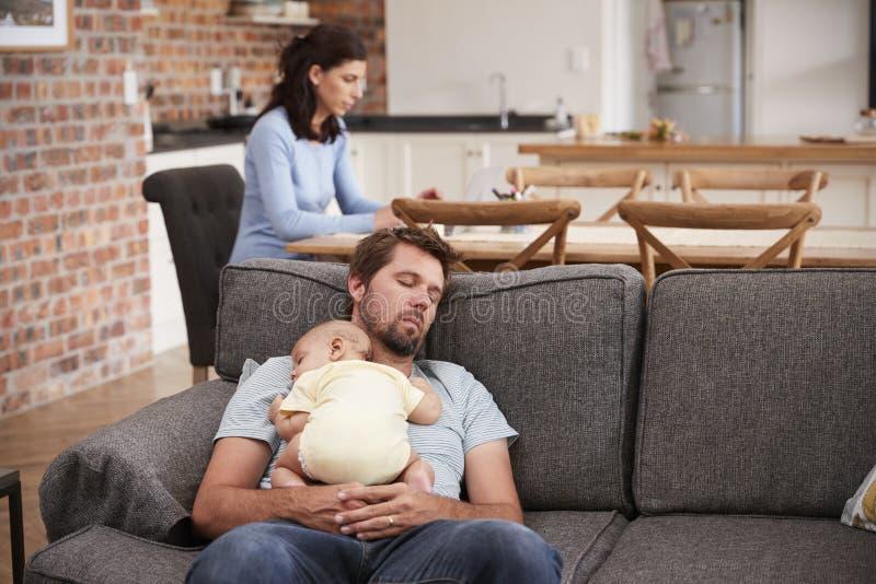 Trött fader With Baby Son sovande på Sofa As Mother Works fotografering för bildbyråer