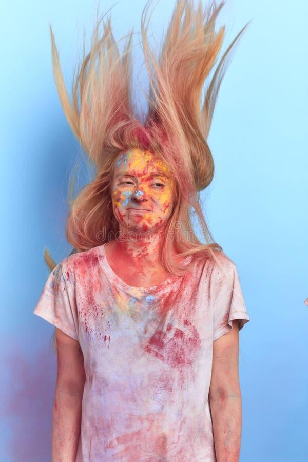 Trött flicka med kulört hår för flyg, kropp och kläder efter Holi färgfestival arkivbilder