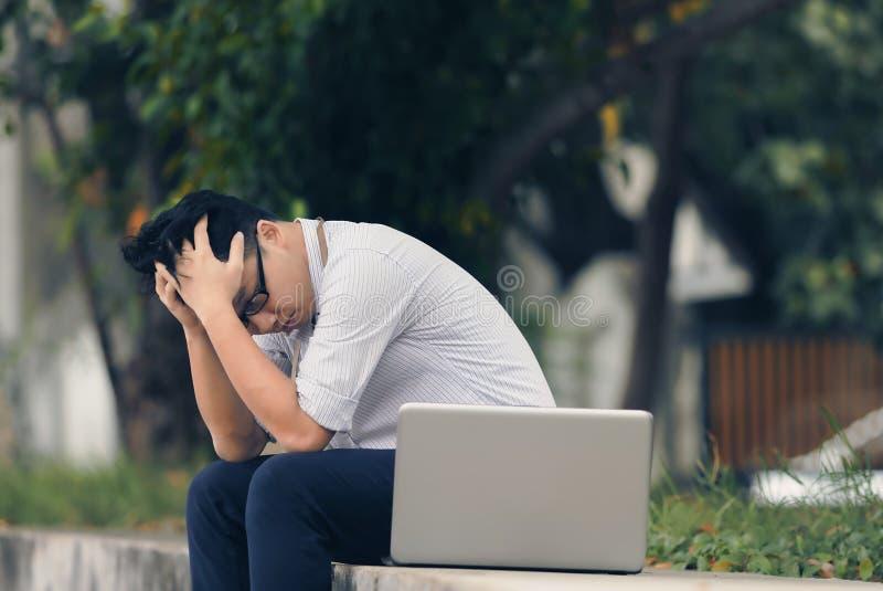 Trött frustrerad ung asiatisk affärsman med bärbara datorn som har problem på det utvändiga kontoret tappning tonad bild royaltyfri bild