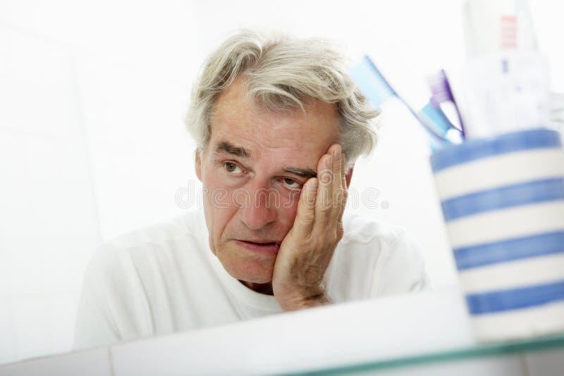 Trött hög man som ser reflexion i badrumspegel royaltyfria bilder