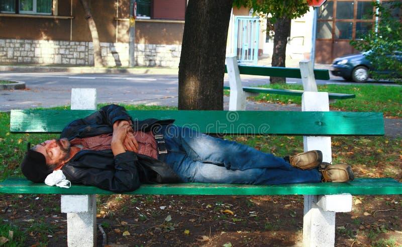 Trött hemlös man som sover på en bänk royaltyfri fotografi