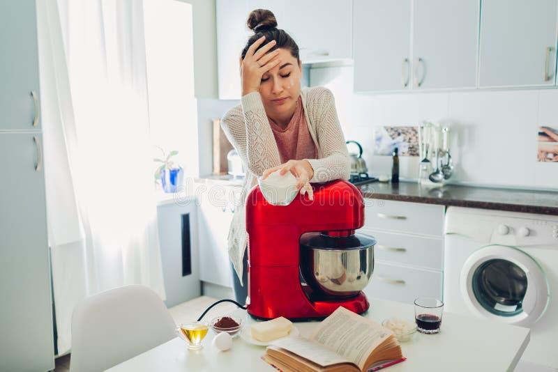 Trött hemmafru som lutar på matberedaren, medan laga mat på kök Invecklat recept arkivfoton