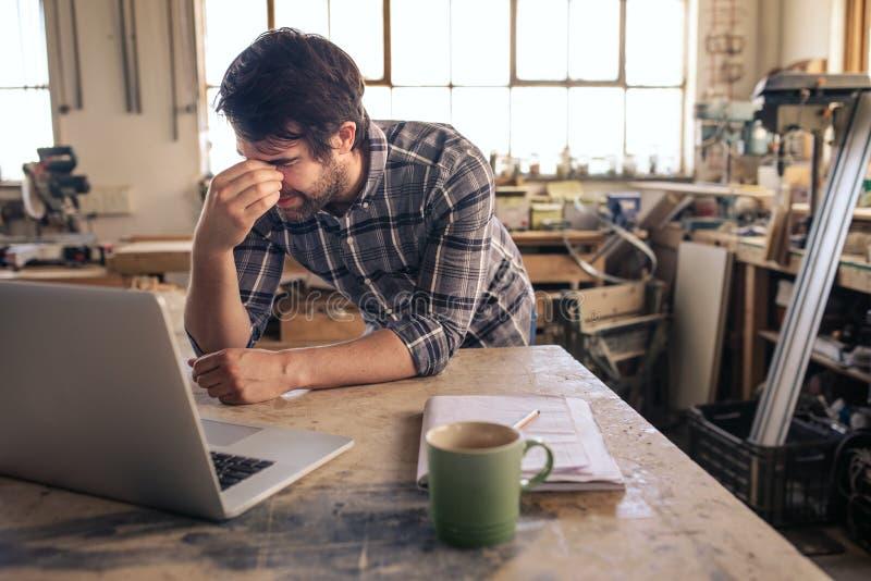 Trött inredningssnickare som arbetar på en bärbar dator i hans snickeristudio royaltyfria foton