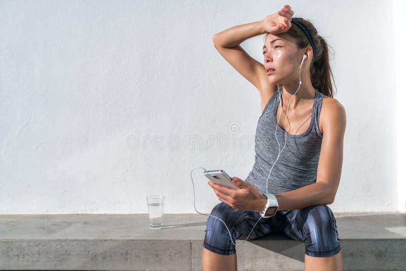 Trött konditionkvinna som svettas att lyssna till musik royaltyfria foton