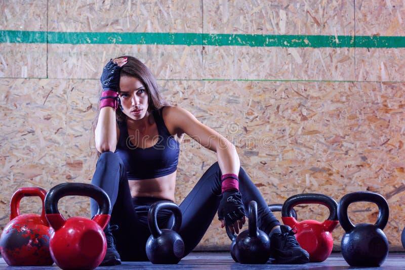Trött konditionkvinnasammanträde och vila på golvet i idrottshall royaltyfri foto
