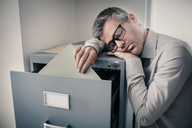 Trött kontorsarbetare som sover i kontoret arkivbilder