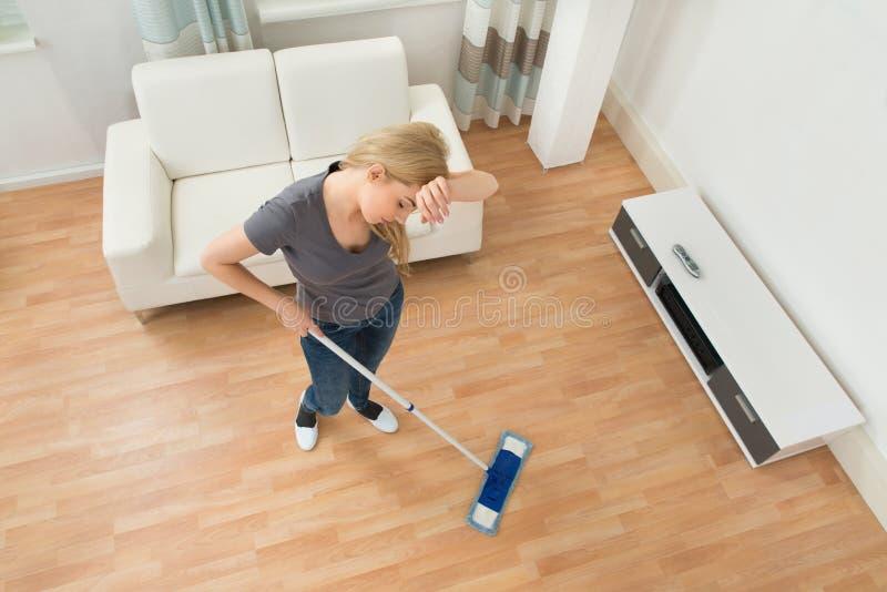 Trött kvinna med golvmopp arkivbilder