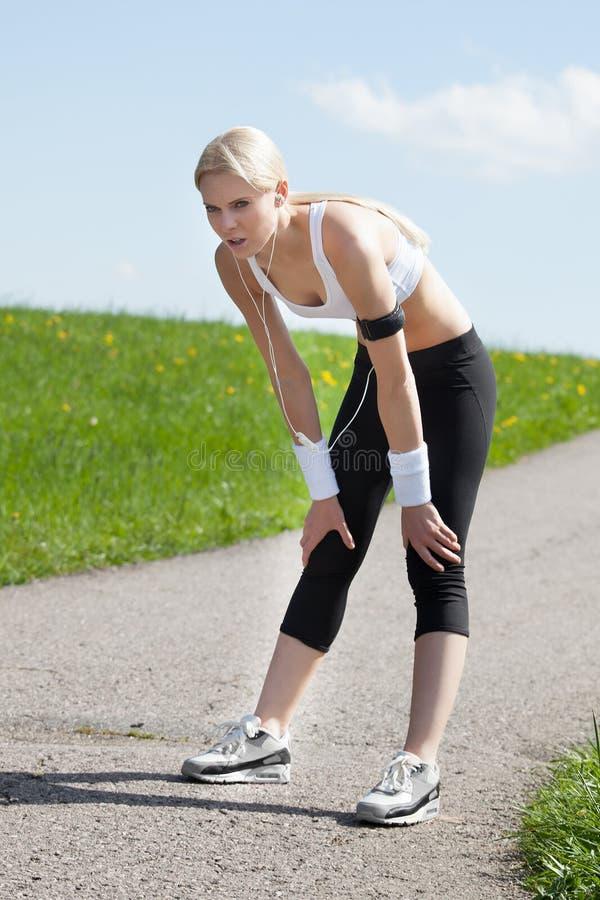 Trött kvinna, når att ha joggat royaltyfri foto