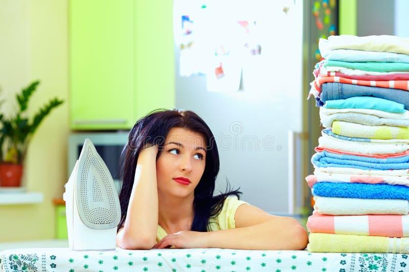 Trött kvinna, når stryka kläder, hemmiljö arkivfoton