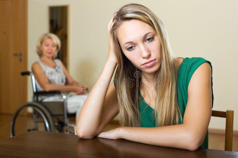 Trött kvinna och rörelsehindrad person arkivfoto