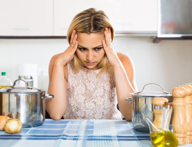 Trött kvinna som lutar henne armbågar på köket royaltyfri fotografi