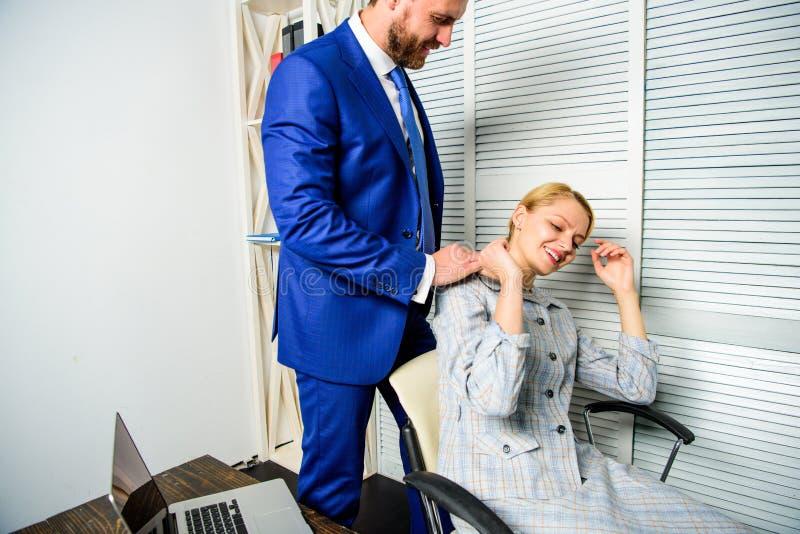 Trött kvinnaarbetare som kopplar av medan man som masserar henne Uppföranderegel och underordnad på arbete Oacceptabelt uppförand arkivfoto
