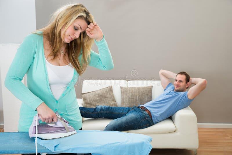 Trött kvinnastrykning medan man på soffan royaltyfri fotografi