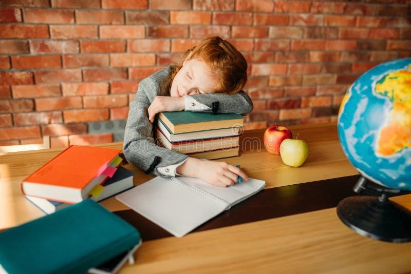 Trött kvinnlig elev sovande på bunt av läroböcker arkivbild