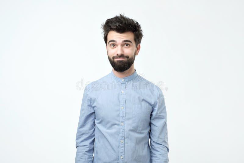 Trött latinamerikansk man i blå skjorta med skägget som confusedly ser på kameran fotografering för bildbyråer