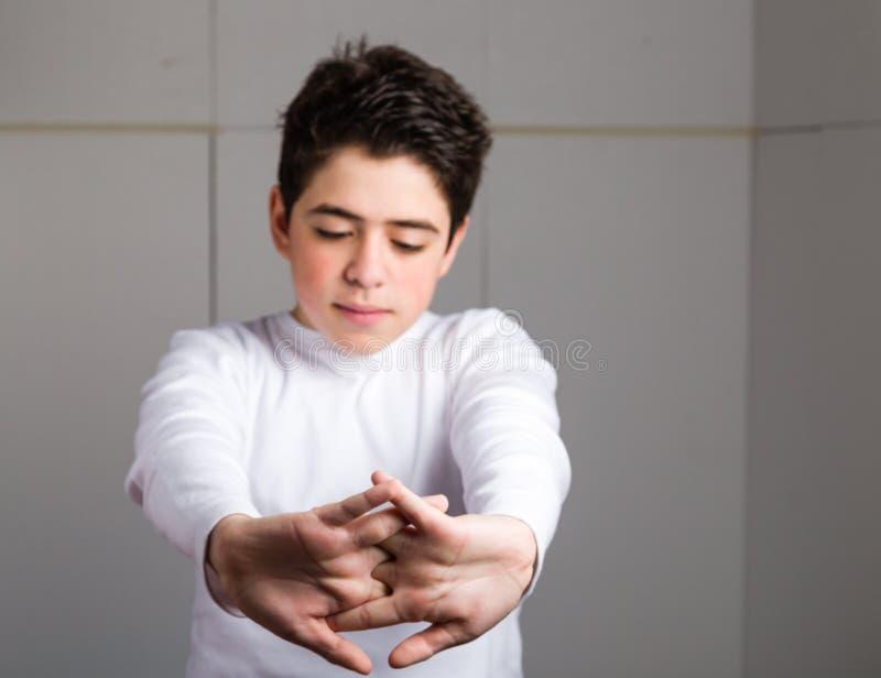 Trött latinamerikansk pojke med aknehud som sträcker hans baksida med clas arkivfoton