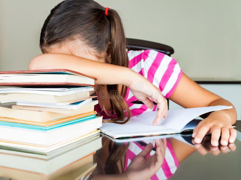 Trött latinsk schoolgirl som sovar på henne skrivbordet royaltyfria bilder