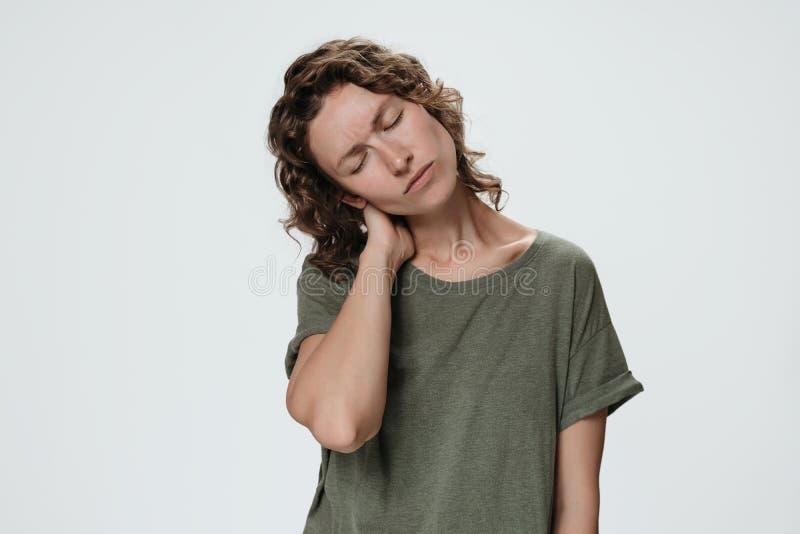 Trött ledsen ung caucasionkvinna som lider från tröttad ut massera styv hals för men royaltyfri foto