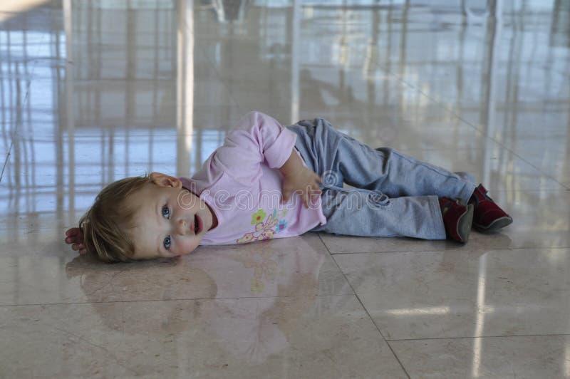 Trött liten flicka som ligger på golvet royaltyfria foton