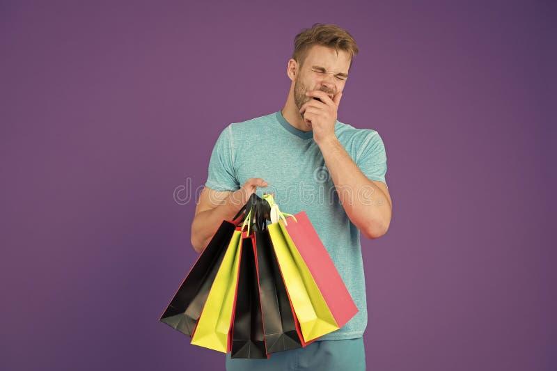 Trött man med shoppingpåsar på violett bakgrund Shopping eller försäljning och cyber måndag Macho med färgrika pappers- påsar arkivfoton