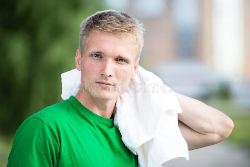Trött man, når tid och att ha övat för kondition Med den vita handduken royaltyfri fotografi