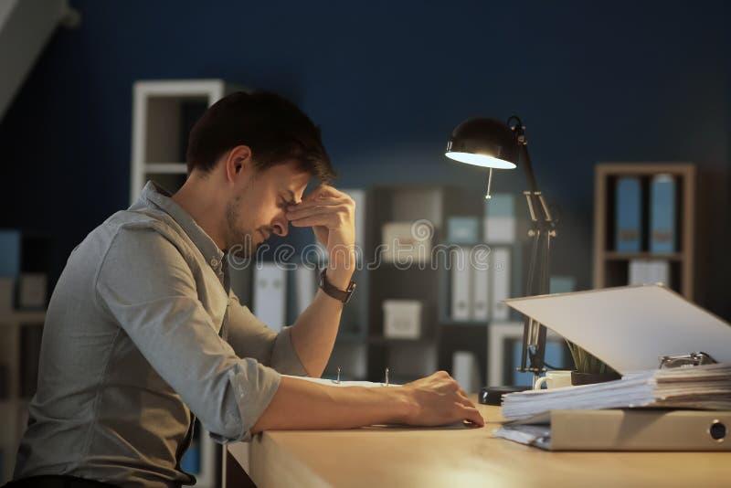 Trött man som sent arbetar i afton royaltyfria foton