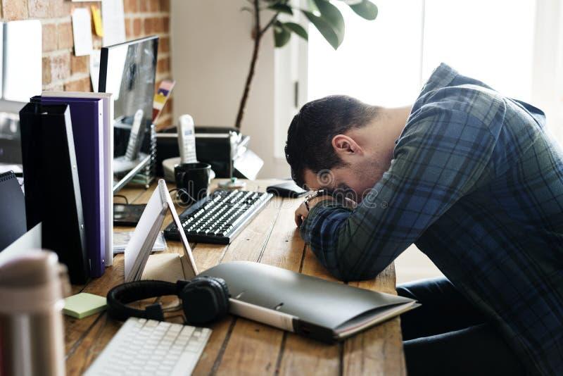 Trött man som ta sig en tupplur på det funktionsdugliga skrivbordet arkivbilder