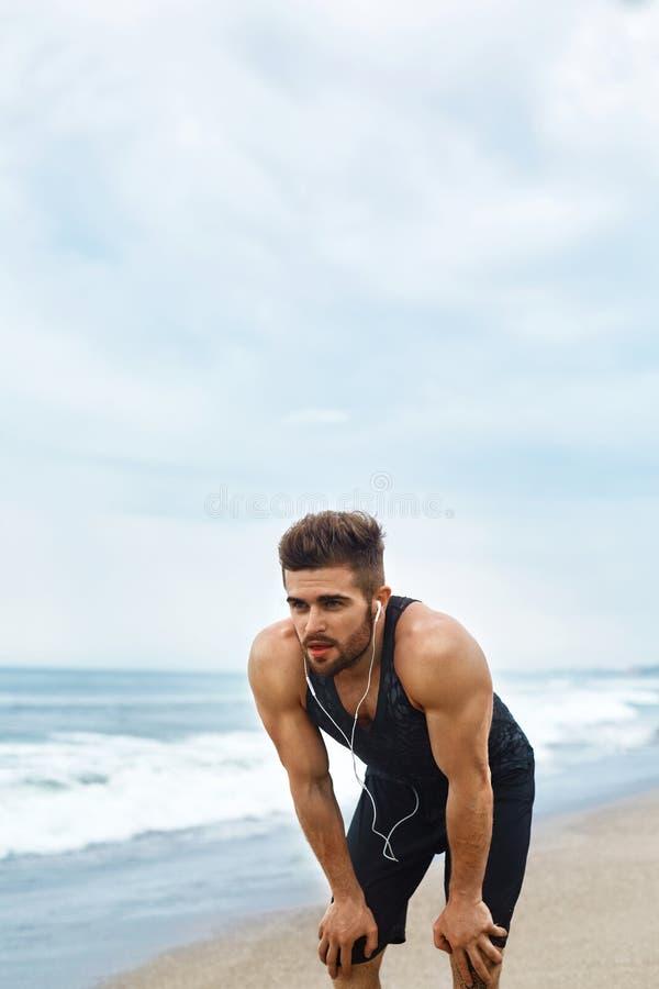 Trött man som vilar, når att ha kört på stranden Utomhus- sportgenomkörare royaltyfri fotografi