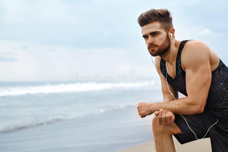 Trött man som vilar, når att ha kört på stranden Utomhus- sportgenomkörare royaltyfri foto
