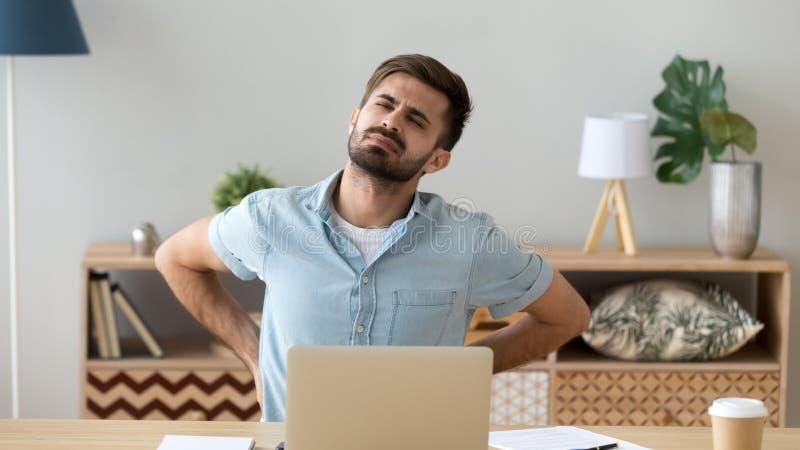 Trött mankänslaryggvärk efter stillasittande datorarbete royaltyfri fotografi