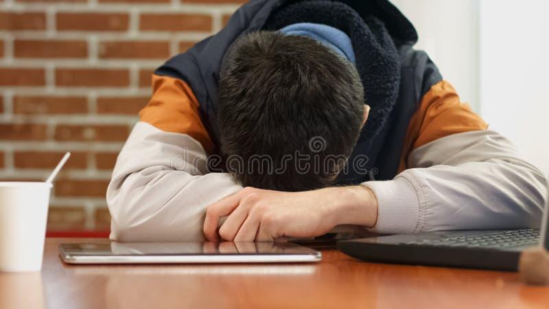 Trött manlig tonåring som sover på skrivbordet, bärbara datorn och minnestavlan på tabellen som borrar arbete royaltyfri fotografi