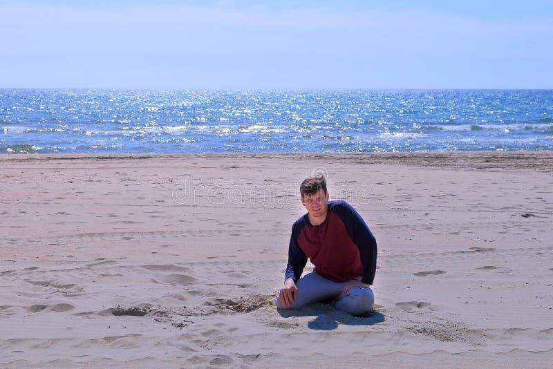 Trött mannedgång för nybörjare på sandstranden, når att ha joggat på sjösidan fotografering för bildbyråer