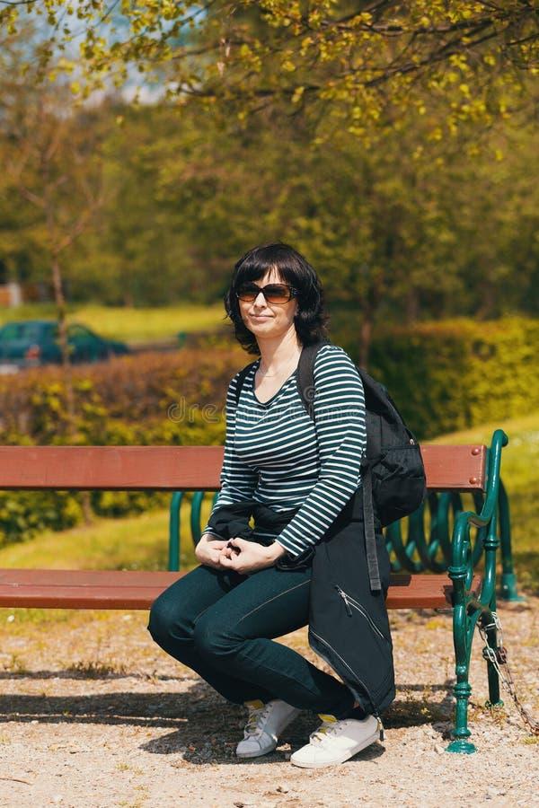Trött mellersta ålderkvinna som vilar på bänk arkivfoton
