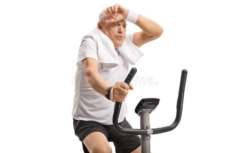 Trött mogen man som rider en motionscykel royaltyfria bilder