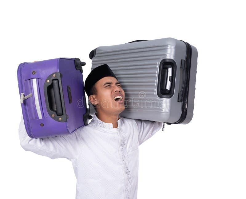 Trött muslim man som bär tung resväska två på hans skuldra royaltyfria foton