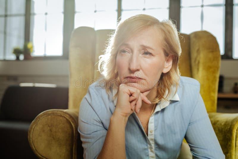 Trött och uppriven blond kvinna som propping hennes haka arkivbild
