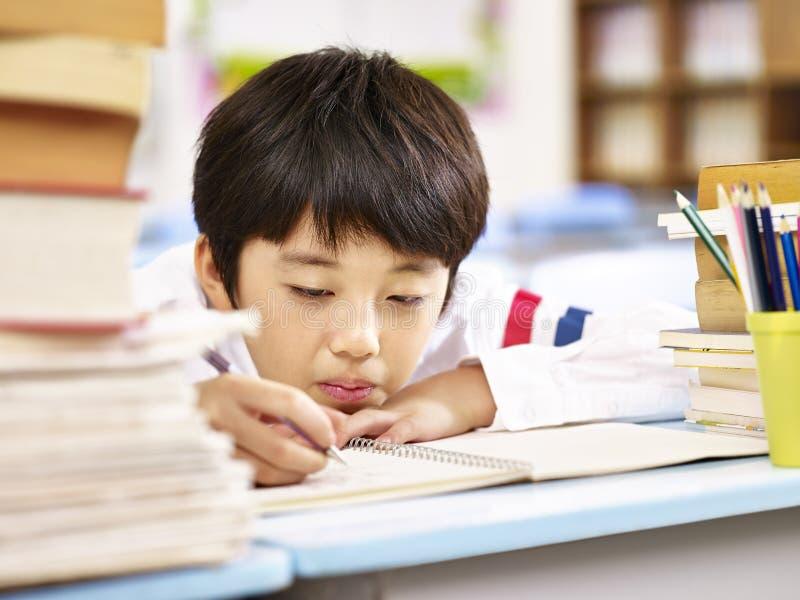 Trött och uttråkad asiatisk skolpojke som gör läxa i klassrum royaltyfri foto
