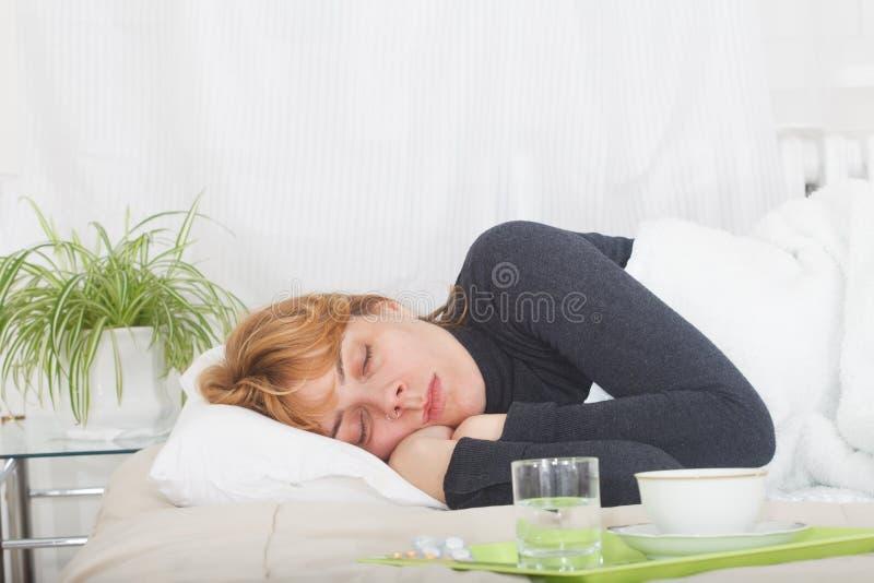 Trött på ung kvinna som sover i säng arkivbilder