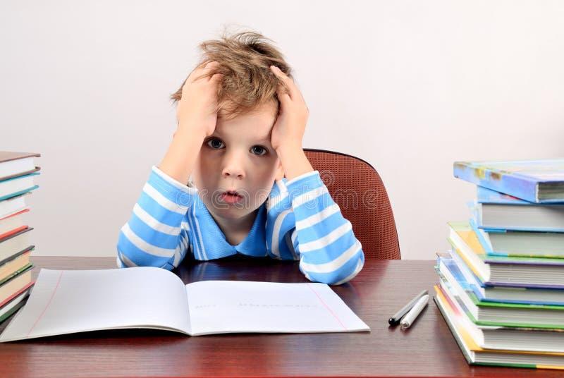 Trött pojkesammanträde på ett skrivbord och innehavhänder till huvudet royaltyfri foto