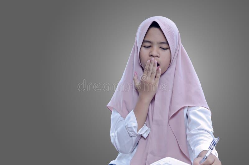 Trött sömnig kvinna som gäspar, arbetar på kontoret och rymmer en penna royaltyfria bilder