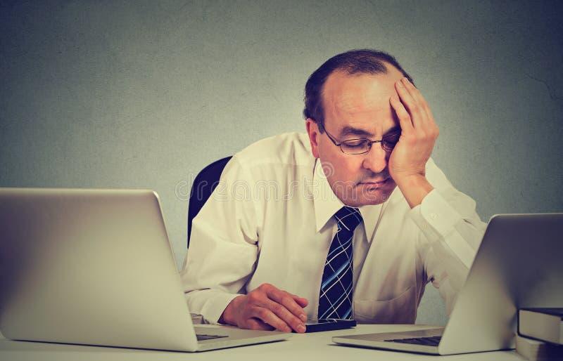Trött sömnigt mansammanträde på skrivbordet med böcker som är främsta av två bärbar datordatorer arkivfoton