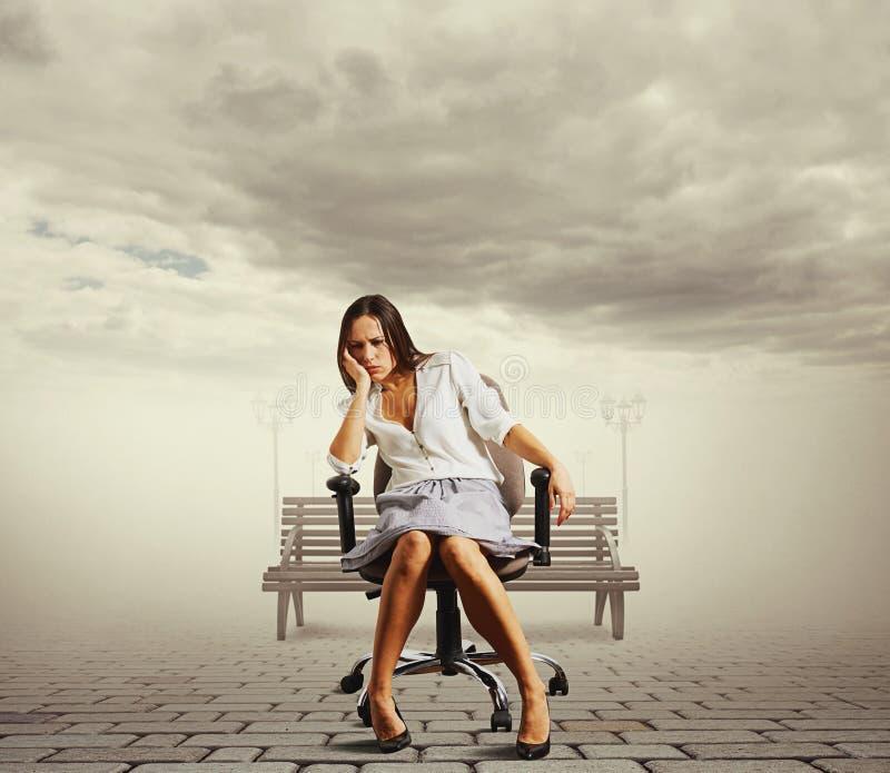 Trött sammanträde för ung kvinna arkivfoto