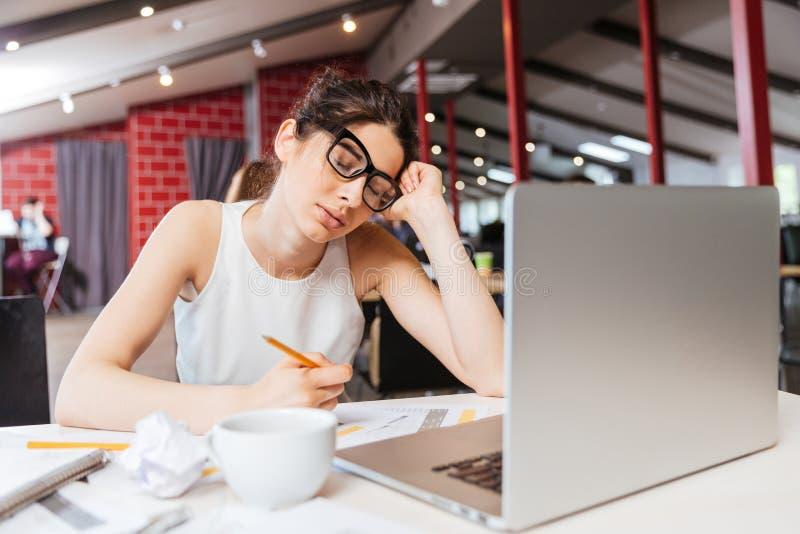 Trött sammanträde och arbete för affärskvinna med bärbara datorn i regeringsställning royaltyfria bilder