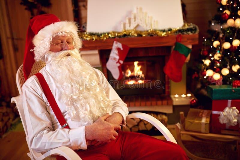 Trött Santa Claus ta sig en tupplur arkivfoto