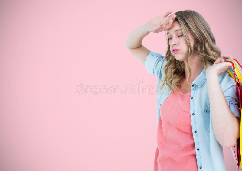 Trött shoppare med påsar mot rosa bakgrund royaltyfria foton