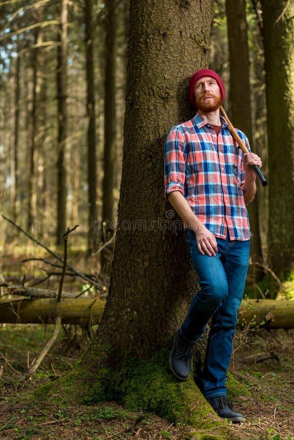 Trött skogsarbetare med vila för yxa royaltyfri foto
