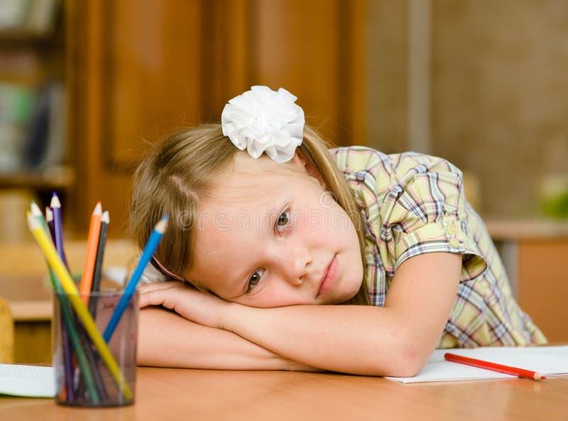 Trött skolflicka i klassrum fotografering för bildbyråer
