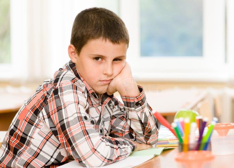 Trött skolpojke i klassrum fotografering för bildbyråer